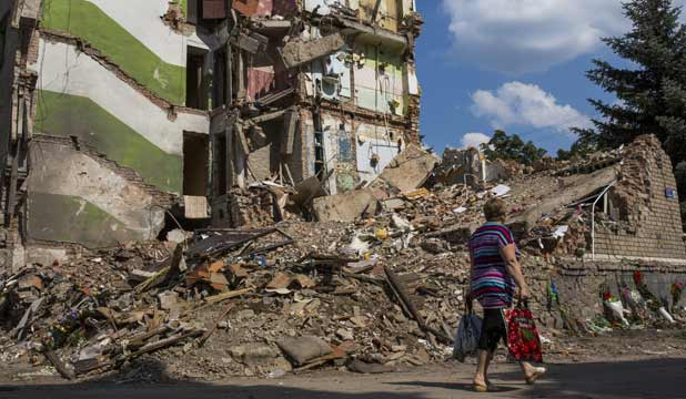 A woman walks past an apartment building damaged rocket fire on Thursday in the rebel stronghold Snizhne, Ukraine.