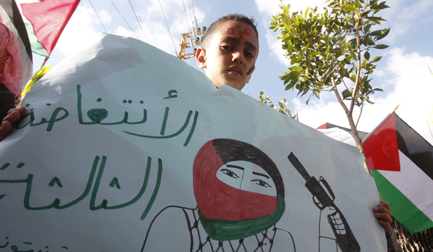"BLEAK WARNING: A Palestinian child carries a banner reading ""The Third Intifada"" in solidarity with the Palestinians in Gaza."