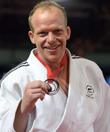 TOUGH NUT: Jason Koster shows off his bronze medal after grinding out a win over long-time rival Duke Didier of Australia.