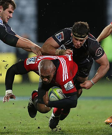 FLYING FIJIAN: Crusaders wing Nemani Nadolo bursts through a Sharks tackle in Saturday's semifinal win.