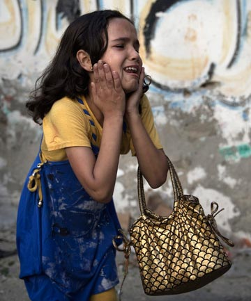 HORROR: A Palestinian girl reacts at the scene of an explosion that medics said killed eight children and two adults, and wounded 40 others at a public garden in Gaza City.