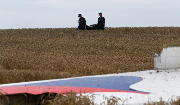 JOB NOT OVER: Ukrainian Emergency Ministry staff carry a body near the wreckage at the crash site of Malaysia Airlines flight MH17. The remains of up to 80 people may still be at the site.
