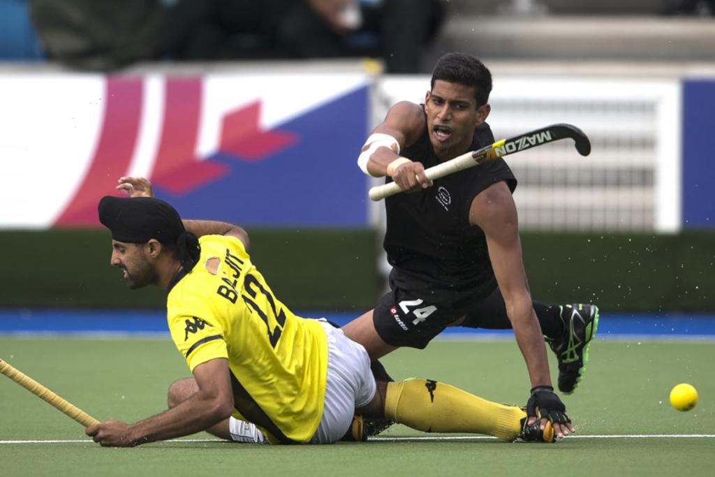 Black Sticks player Arun Panchia has his legs taken out by a Malaysian opponent.