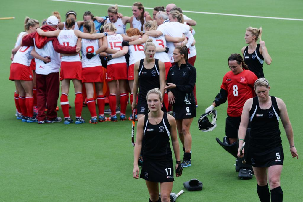 Dejected Black Sticks players walk from the turf as England huddle in celebration.