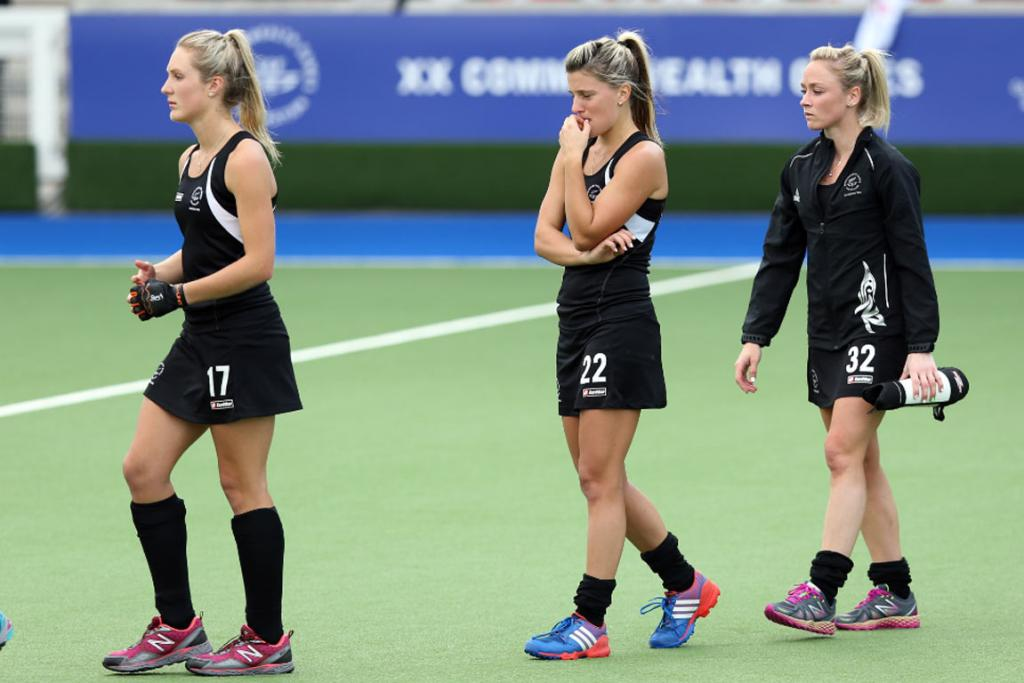 Sombre Black Sticks Sophie Cocks, Gemma Flynn, Anita Punt line up to shake hands with England.