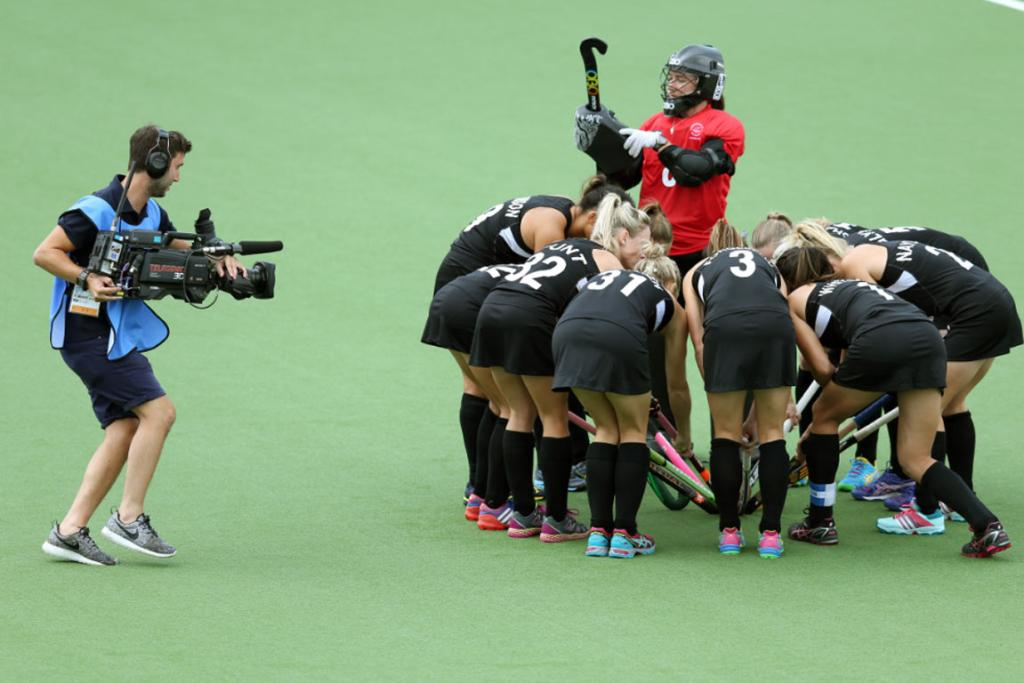 Under the gaze of a TV camera, the Black Sticks huddle before their semifinal against England.