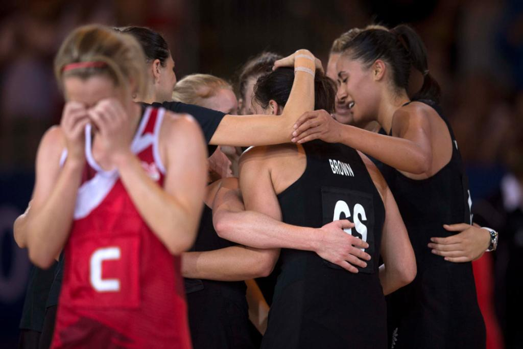 Silver Ferns players celebrate as England's centre walks off the court in tears after their semifinal.