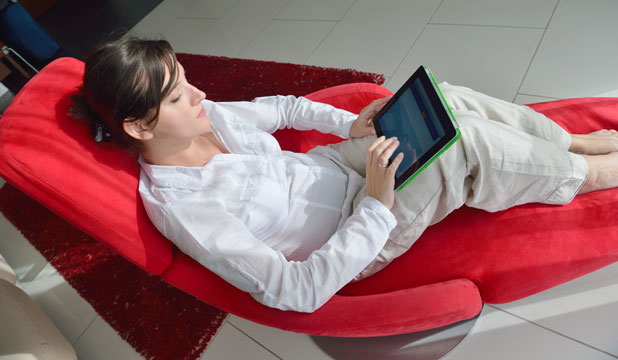 Woman relaxing reading a digital tablet