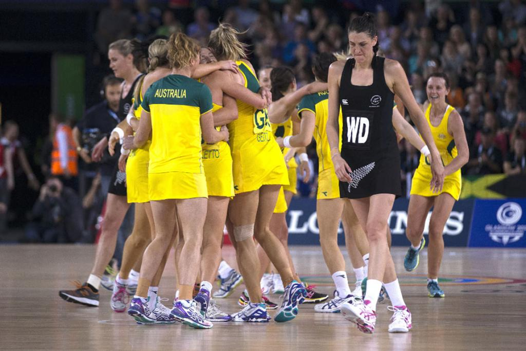 Anna Harrison walks from the court as the Australians celebrate victory.