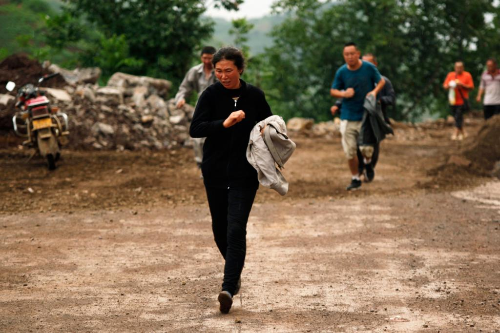 People run past a hillside at risk of landslide after the earthquake.