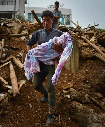GRIM TASK: Mao Changxue carries the body of his son after it was dug out from the debris of their home, which collapsed in the earthquake.