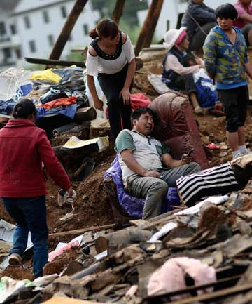 AGONY: Liu Jiali, centre, sits on a sofa next to his collapsed house as rescuers try to find his wife and child buried in the rubble.