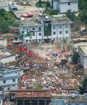 RESCUE MISSION: A helicopter flies above collapsed houses following the earthquake.