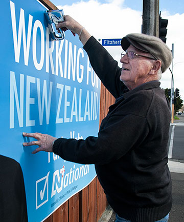 BACK UP AGAIN: Roy Le Quesne restores National Party signs that were vandalised.