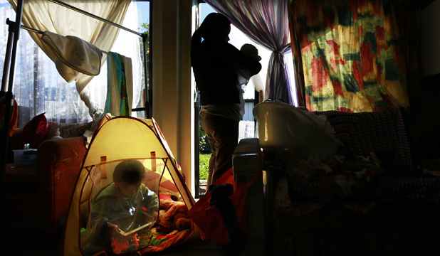 BLEAK START: A mother holds a six-day-old baby, with her 34-month-old playing in a pop-up tent in the refurbished shed they rent.