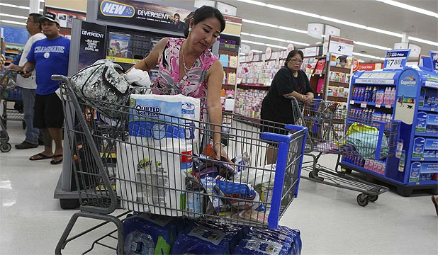 STOCKING UP: Shelly Nakasone buys supplies in Mililani as a hurricane and a tropical storm approach the Hawaiian islands.