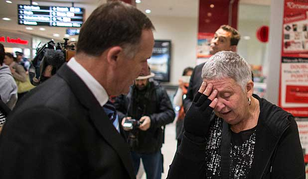 TEARFUL: Paulette Barr uses newspapers to try and stop cold draughts through her quake-hit home.