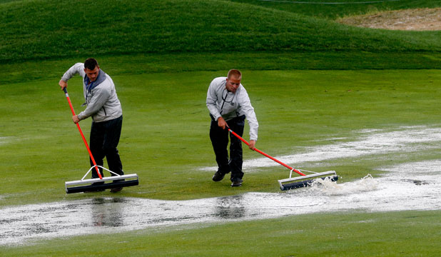 DOWNPOUR DELAY: Workers at Valhalla sweep water from a fairway on the morning of the final day at the PGA Championship.