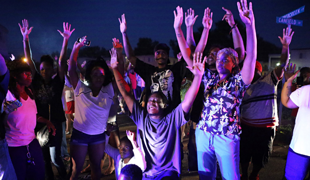 DON'T SHOOT US: Angry protesters raise their hands and plead with police not to shoot them Saturday night in Fergusson, Missouri.