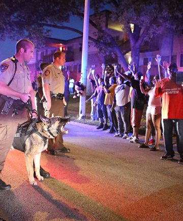 Police officers confront a crowd they're trying to break up a demonstration in Ferguson, Missouri, on Saturday night.