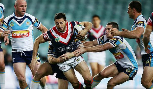 HARD TO HOLD: Roosters fullback Anthony Minichiello tries to give the Gold Coast defence the slip.