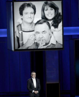 Actor Robin Williams speaks onstage during the 65th Annual Primetime Emmy Awards in 2013 as a picture of him in the cast of TV show Mork and Mindy is screened behind him.