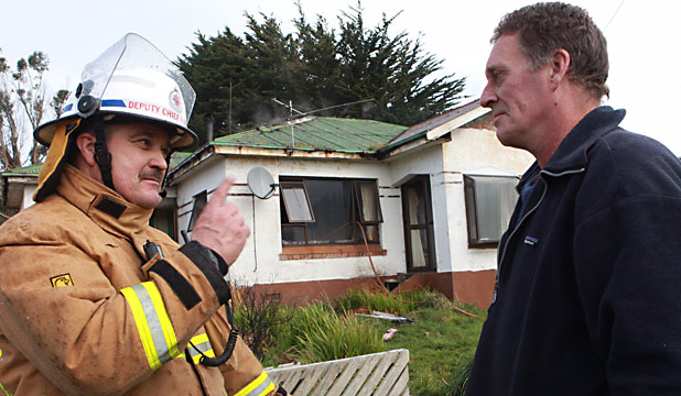 IN SHOCK: Michael Hawke speaks with volunteer fire brigade deputy chief Paul Taylor after his rented house was seriously damaged in a fire.