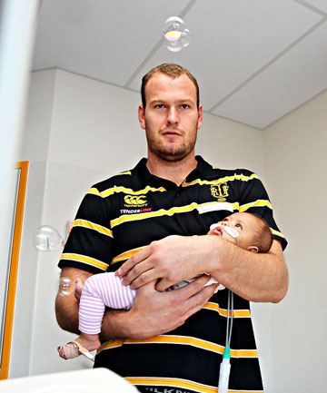 Taranaki rugby player, James Broadhurst holding Faasuka Etimani. Taranaki rugby players visited the sick children in the children's ward at the Taranaki Base Hospital.