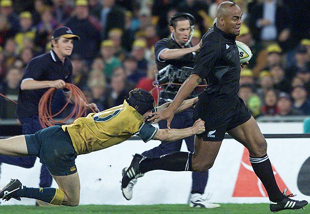 THAT TRY: Jonah Lomu evades the tackle of Stephen Larkham to cross for the match-winning five-pointer in the All Blacks famous Bledisloe Cup victory at Sydney in 2000.