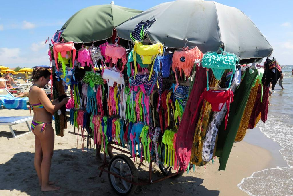 A woman looks at swimsuit on a beach at Maccarese neighbourhood of Rome.