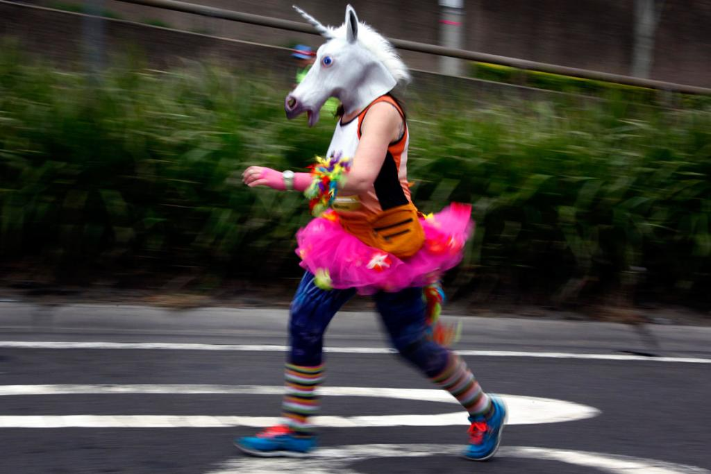 A woman wearing a mask and costume runs during the start of the 44th annual City2Surf fun run .