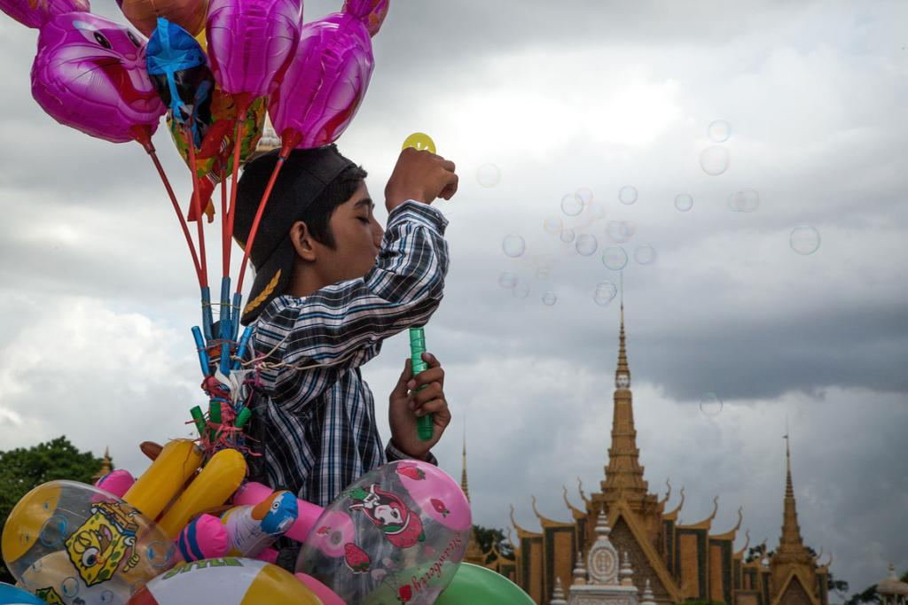 A young balloon seller blows soap bubbles to attract tourists in front of the Royal Palace in Phnom Penh, Cambodia.