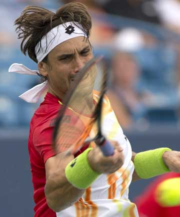 David Ferrer returns a shot against Julien Benneteau in a men's singles semifinal of the Western and Southern Open tennis tournament in Cincinnati.