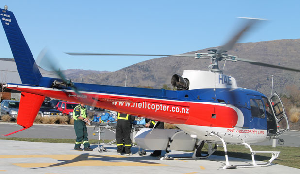 CHOPPER DOWN: An injured man is taken from a helicopter to the Wanaka Medical Centre. Six of the seven people onboard a helicopter that crashed on Mt Alta near Wanaka at 12.20pm on Saturday were injured. One person died.