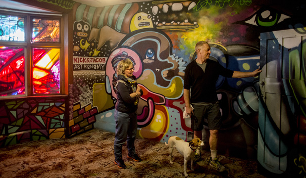 ART HOUSE:  Greg and Maree Johnston with their dog Tagen view some of the street art in Ren Bell's bungalow, which is due to be demolished this week,