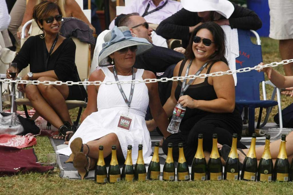 Guests sit with a row of champagne bottles during the Concours d'Elegance at the Pebble Beach Golf Links in Pebble Beach, California. The Concours tops a week-long celebration of automobiles and car culture on the Monterey Peninsula.