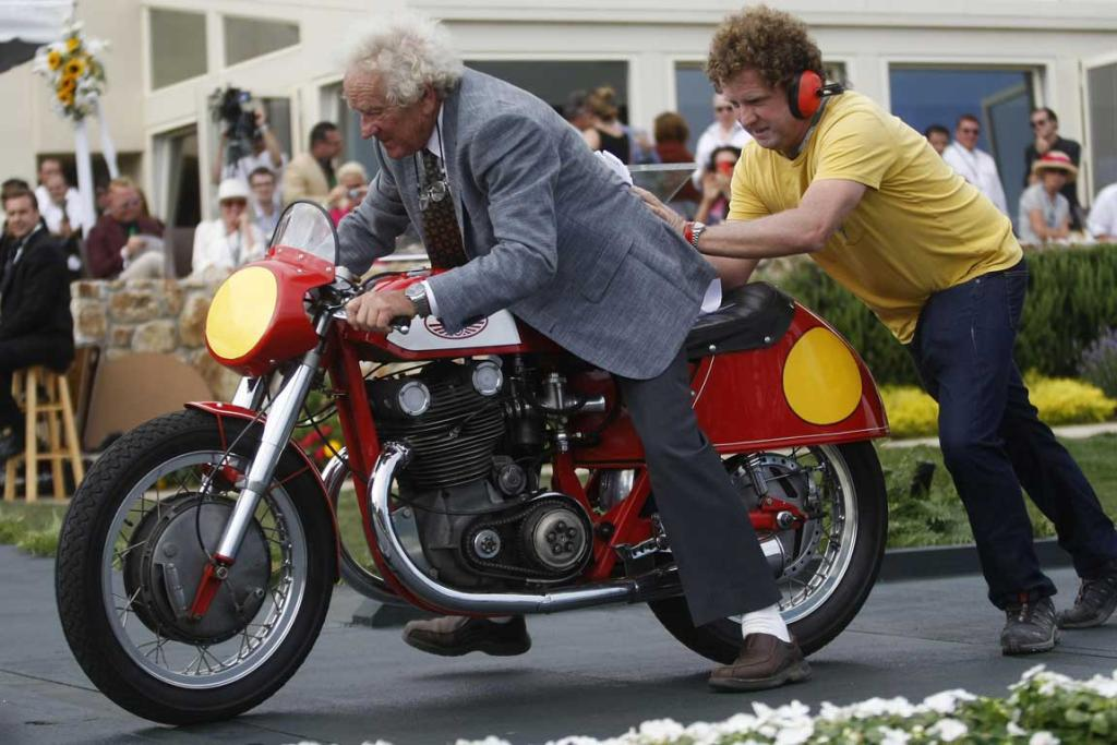 An entrant is pushed off stage on his Jawa Motors motorcycle after receiving an award during the Concours d'Elegance in Pebble Beach, California. The Concours tops a week-long celebration of automobiles and car culture on the Monterey Peninsula.