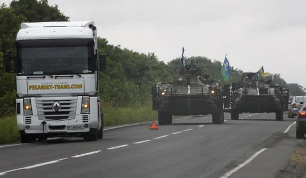 Ukrainian servicemen drive armoured vehicles along a road as they patrol the Donetsk region