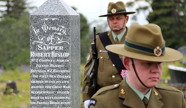 PAYING RESPECT: Members of the New Zealand Defence Force surround Sapper Robert Arthur Hislop's headstone at Waikumete Cemetery during his service today.