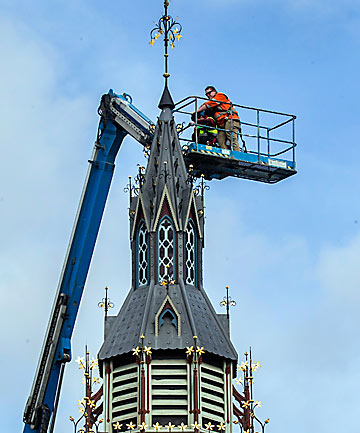 BACK TOGETHER: The spire is replaced on the repaired and strengthened clock tower on Victoria Street.