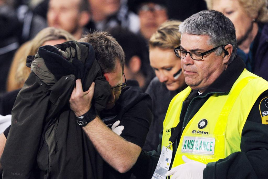 A St John ambulance officer attends to a man injured by fireworks at the start of the Bledisloe Cup match at Eden Park.