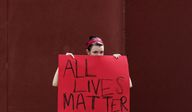 PEACE AT LAST: A woman protesting for the killing of unarmed teen Michael Brown holds a placard towards unseen supporters of officer Darren Wilson.