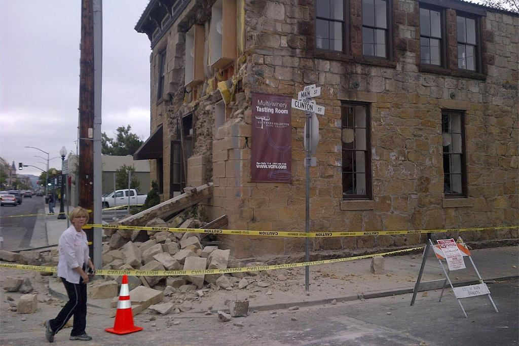 An unidentified woman walks past damage to a downtown building in Napa, California.