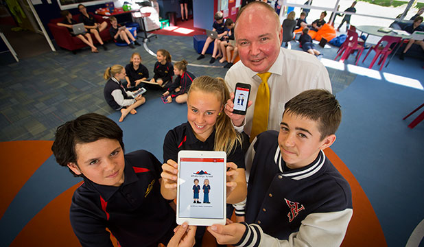 Whakaronga School students Finnley Wineera, 13, left, Phoebe Phillips, 12, and Jack Carey, 13, with principal Jaco Broodryk show off the school's new mobile app.
