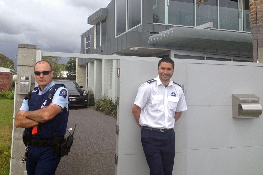 A police officer and security guard outside the home of AC/DC drummer Phil Rudd.